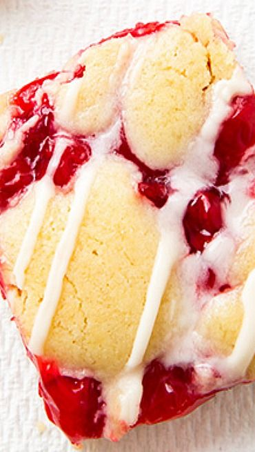 Cherry Pie Bars Recipe ~ a buttery almond flavored cookie like batter which is topped with that simple yet incredible cherry pie filling, then it's topped with more dollops of the batter and it's baked to light golden perfection. It's finished with a rich and creamy vanilla almond flavored glaze.
