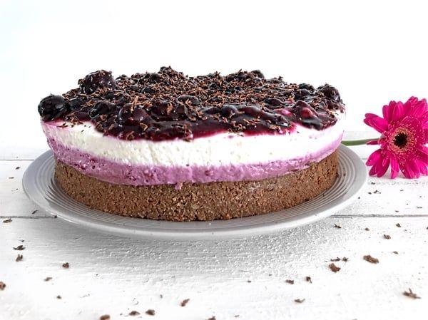 Een glutenvrije chocolade brownie gecombineerd met een heerlijke bessen laag en een fluweel zachte vanille creme afgetopt met een coulis van blauwe bessen.