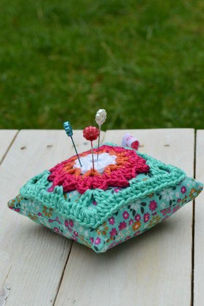 Speldenkussentje, een leuk gehaakt granny-patroon is genaaid op een kussentje van een vrolijk stofje. In de kleuren wit, roze, oranje en mintgroen.