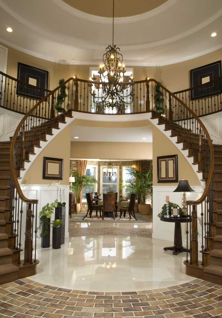 Round Two Story Foyer With Stairs Winding Down Both Sides Of The Room At Bottom Off Is A Brick Floor Landing Leads Into Formal Dining