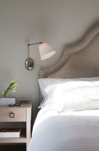 Serene bedroom features swing-arm sconce on light gray wall framing gray  linen headboard with silver nailhead trim accented with crisp white bedding  next to ...