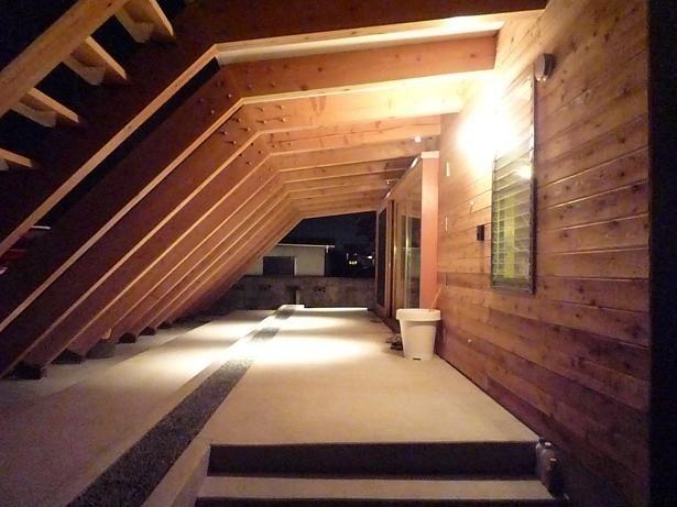 深い軒がかかったテラス夜景。張り出した13本の梁がまるでトンネルのように見えます。半屋外的なこの場所はリビングの延長としても機能しています。 専門家:小磯一雄|KAZ建築研究室が手掛けた、屋外テラス夜景(群馬県太田市・芝屋根住宅-1|mat house)の詳細ページ。新築戸建、リフォーム、リノベーションの事例多数、SUVACO(スバコ)