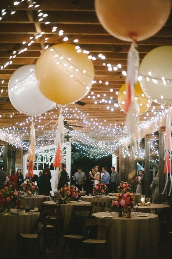 whimsical wedding reception decor look with giant balloons and twinkly lights / http://www.himisspuff.com/string-bistro-lights-wedding-ideas/13/