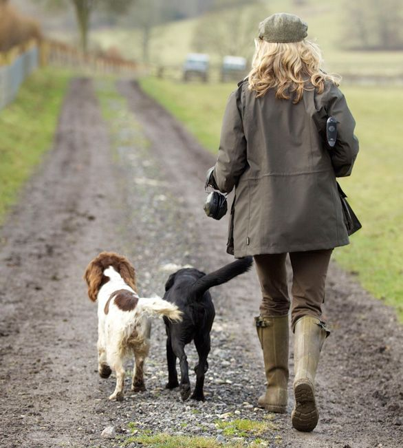 Barbour Women's Sporting collection model walking with two dogs