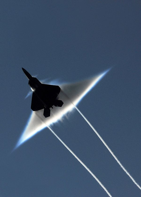 Air Force F-22 Raptor executes a supersonic flyby over the flight deck of the aircraft carrier USS John C. Stennis (CVN 74)