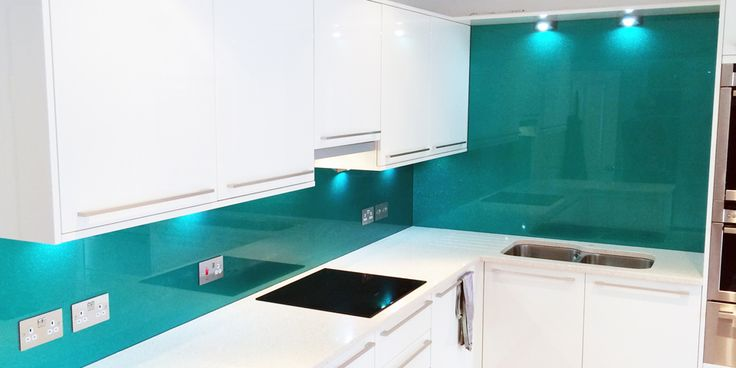Kitchen fitted with bespoke teal sparkling metallic finish glass splashbacks