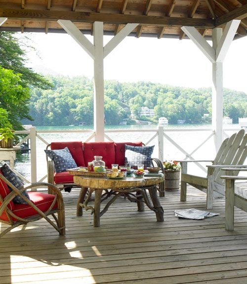 Adirondack chairs and midcentury bentwood seating, as well as a coffee table crafted by a local artisan, furnish the boathouse deck. The blue-and-white pillows are from Restoration Hardware.