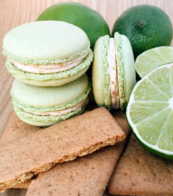 Key Lime Crumble Macarons: A perfected 3 ingredient key lime curd sets atop white chocolate graham cracker ganache. Treat yourself to this simple, fresh, tart, sweet, and delicious crowd-pleaser now! #macarooz #keylimemacarons #keylimecrumble #springdessert #keylimefrenchmacarons