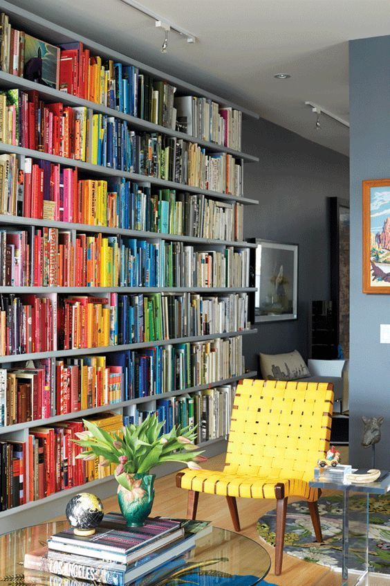 An ordinary bookcase is transformed into a rainbow of colour when books are arranged by hue.