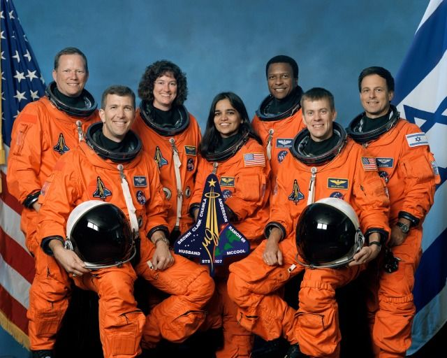 Mission success for the crew of COLUMBIA shuttle flight STS-107. Seated from left are Rick D. Husband, mission commander; Kalpana Chawla, mission specialist; and William C. McCool, pilot. Standing from left are David M. Brown, Laurel B. Clark, and Michael P. Anderson, all mission specialists; and Ilan Ramon, payload specialist from the Israeli Space Agency.