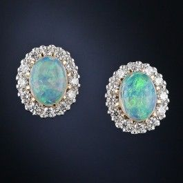A bright and lively pair of opals, with a predominately blue and green coloration with orange flashes, glow from within sparkling diamond halos in these gorgeous and very wearable earrings, newly made in 18 karat yellow and white gold. 1/2 inch by 7/16 inch.