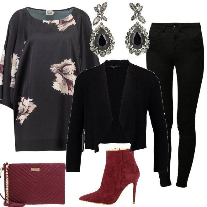 Un paio di jeans neri si trasformano in proposta elegante se abbinati ad una casacca con motivi floreali e ad una giacca corta. Le scarpe sono dei tronchetti con tacco alto e la borsa è una pochette, entrambe color burgundy. Un paio di orecchini con pendenti completa la proposta.
