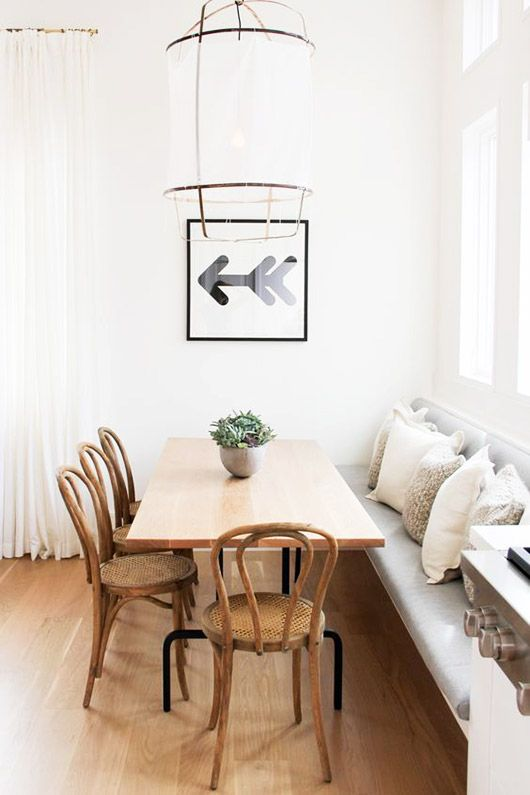 sleek padded bench with wood table and chairs in white kitchen with unique light fixture and arrow wall art / sfgirlbybay