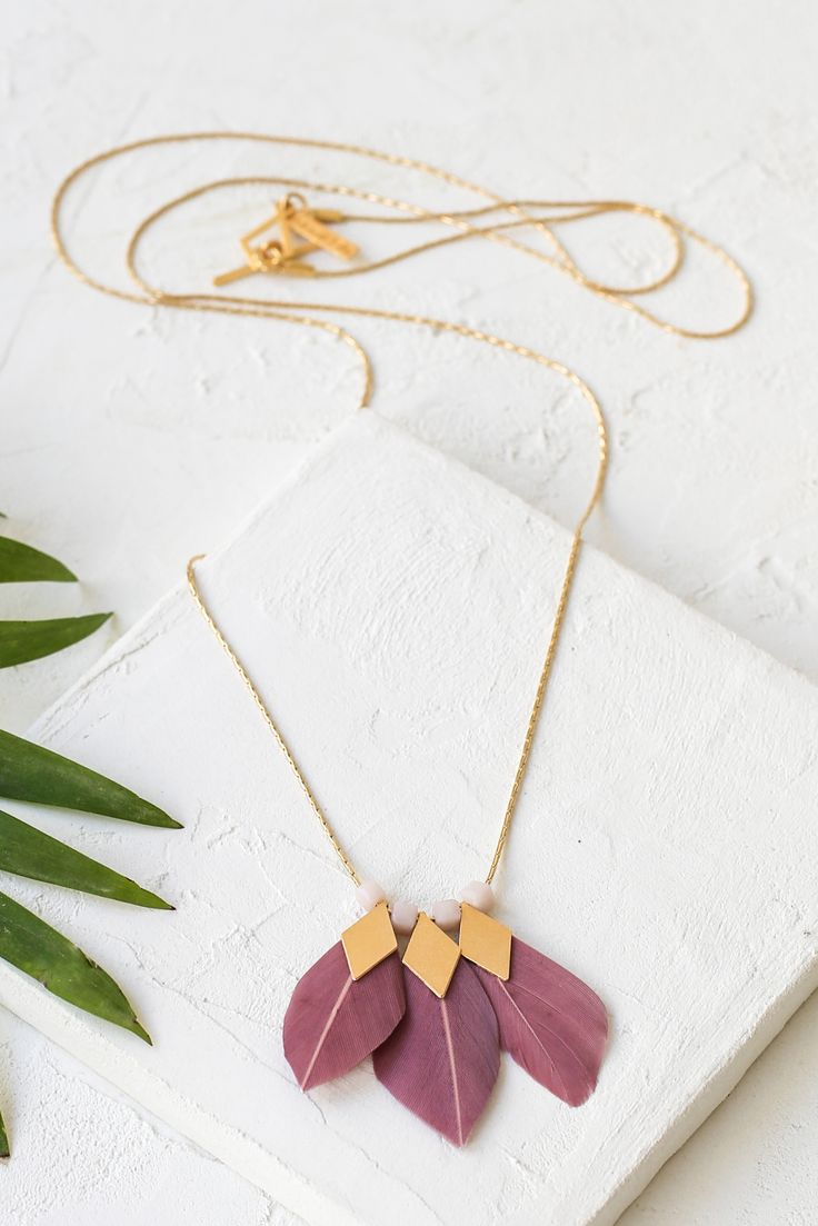 Canary necklace by Shlomit Ofir. A long necklace with three purple feathers with geometric golden elements and glass beads.