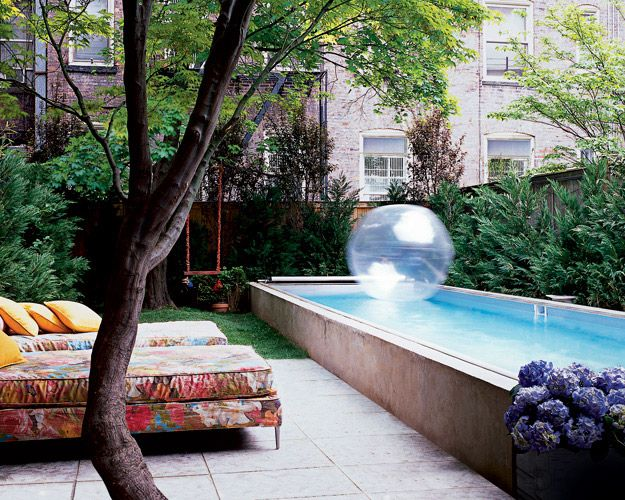 Cynthia Rowley's backyard.  In the garden, midcentury chaise lounges are upholstered in a Mulberry fabric from Lee Jofa.