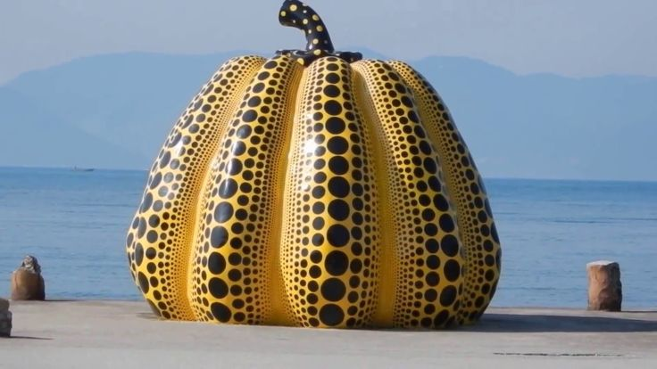 Yayoi's yellow pumpkin with black polka dots on Naoshima island in Japan's Seto Inland Sea . The collection of museums and artworks set among the island known as Benesse Art Site. Quintessential : sculpture of an enormous yellow pumpkin speckled with rows of black dots. Created by Japanese artist Yayoi Kusama in 1994, the giant gourd sits at the end of a pier near Benesse House, a Tadao Ando-designed art museum and hotel complex.