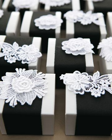 Favor boxes with marshmallows and local hot cocoa mix are wrapped in black grosgrain ribbon and topped with lace flowers.