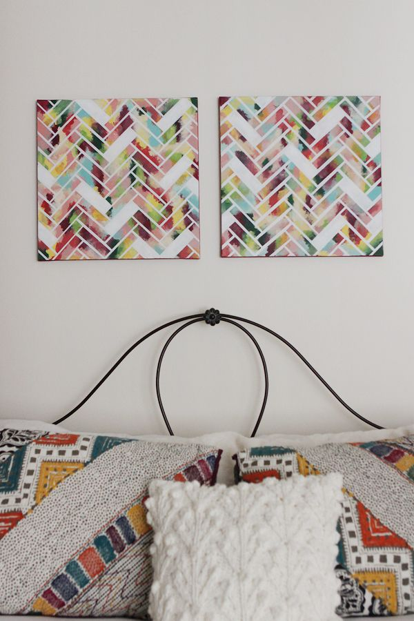 The DIY artwork: 1) Paint whole canvas in different colors 2) Cut strips of painter's tape of the same size 3) Tape them onto the canvas in a herringbone pattern leaving some out 4) Spray paint whole canvas in white. 5) Finish painting edges of canvas.