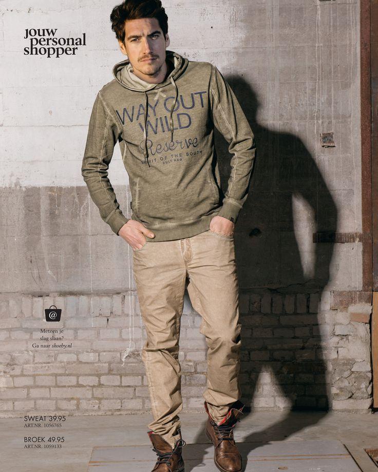 GO WILD! Collectie. Legergroene trui met beigekleurige broek.