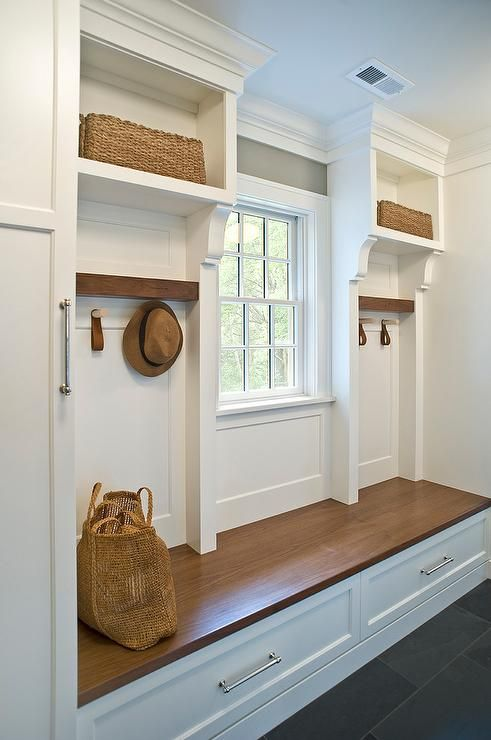 A custom wood mudroom bench displays a white finish with handsome framed moldings, while a natural wood finish makes up the seating bench.