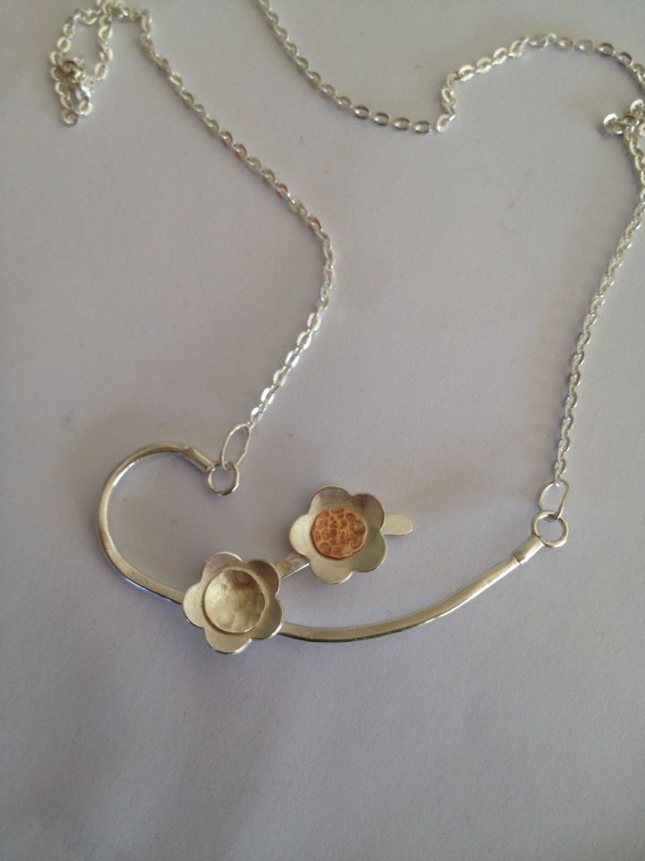 Silver and organic copper and silver flower necklace .