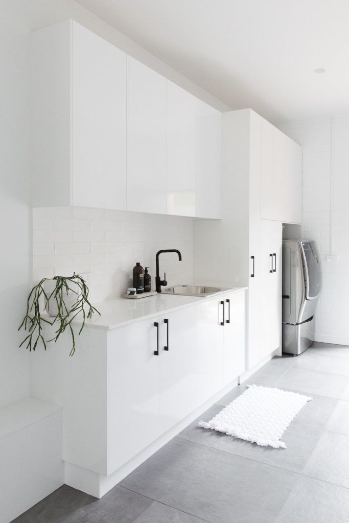 Large and contemporary white laundry with grey floor tile. Modern and streamlined laundry with black handles and accessories.
