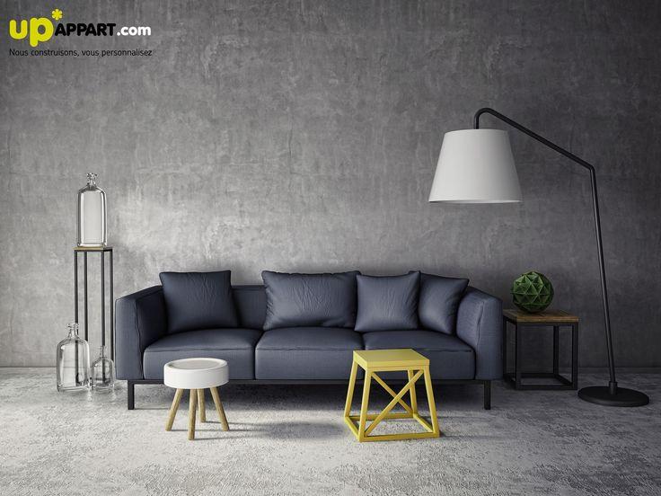 Un salon en béton, aux couleurs sombres et lignes élégantes.