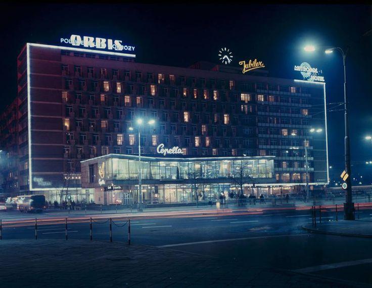 """Marszałkowska w roku 1974. Na pierwszym planie zaprojektowany w 1966 przez Zygmunta Stępińskiego budynek """"Cepelii"""". Z charakterystycznym neonem. Nad nim Hotel Metropol z neonami""""Jubiler"""" i """"Orbis"""" Źródło:Kadr z filmu """"Neon"""" Erica Bednarskiego. *Adrian*"""