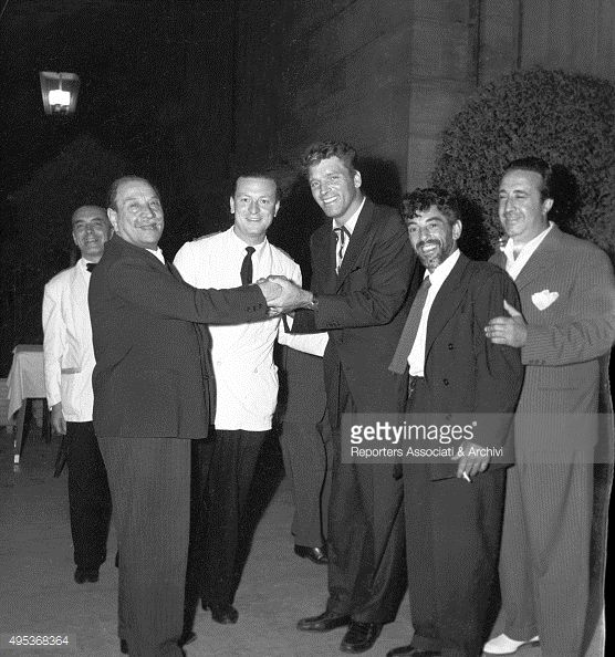 American actor Burt Lancaster smiling while shaking hands with Italian chef Alfredo, the owner of the famous restaurant in Rome bearing his name. Rome, 1959  (also pictured, Lancaster's BFF Nick Cravat second from right)