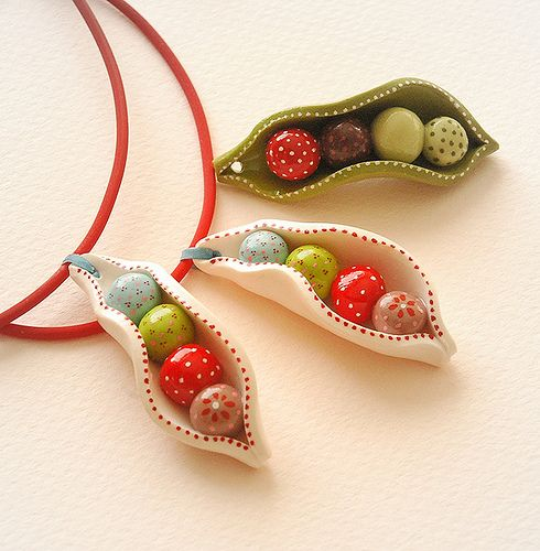 Eva Thissen, polymer clay. Peas in a pod sitting straight in a row. This pretty peas-in-a-pod pendant in green colour is crafted and painted individually. Each piece of one theme is therefore unique and slightly different to one another. The pendant is sealed with two coats of gloss varnish.  Comes with 40cm long red rubber choker with stainless steel clasp. Size of the clay pendant; approx. 20mm x 50mm diameter.  Where to buy: margrietje.etsy.com