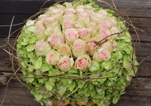 Bloemstuk van groene hortensia's met rozen
