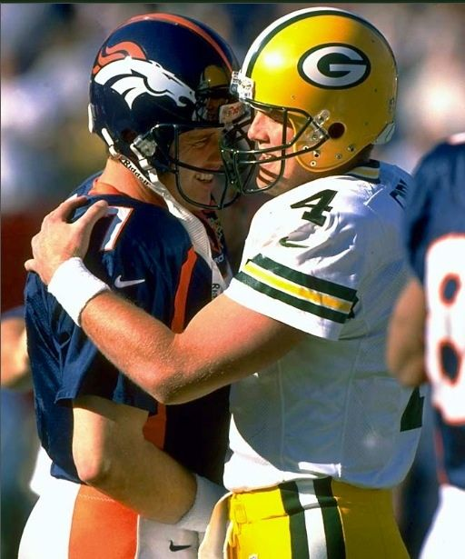 Dever Broncos John Elway #7 Brett Favre #4 stop for a moment to give each other a quick embrace. Moments from the past.