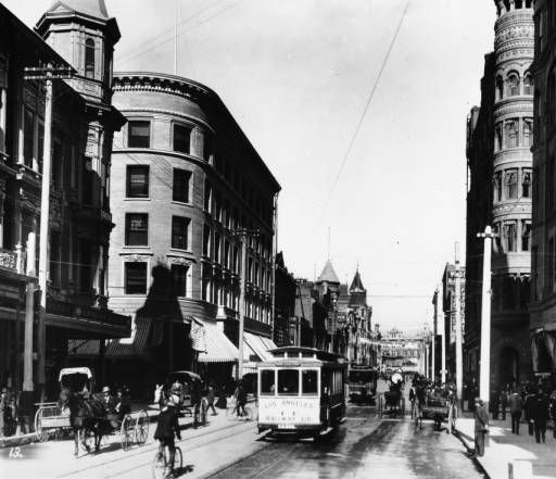 """Photo of Downtown Los Angeles street with Los Angeles Railway streetcars, bicycles and horses with carriages on newly paved roads :: """"Dick"""" Whittington Photography Collection, 1924-1987"""