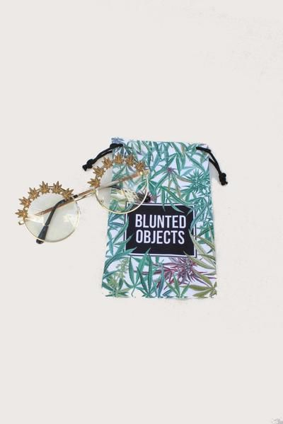 Down the rabbit hole you go with these whimsical clear lens glasses featuring weed leaves fanned across the frame. Blunted Objects microfiber pouch included. Handmade in Los Angeles.  MeasurementsLens: 52 x 52mm Nose Bridge: 22mmTotal Width: 122mm