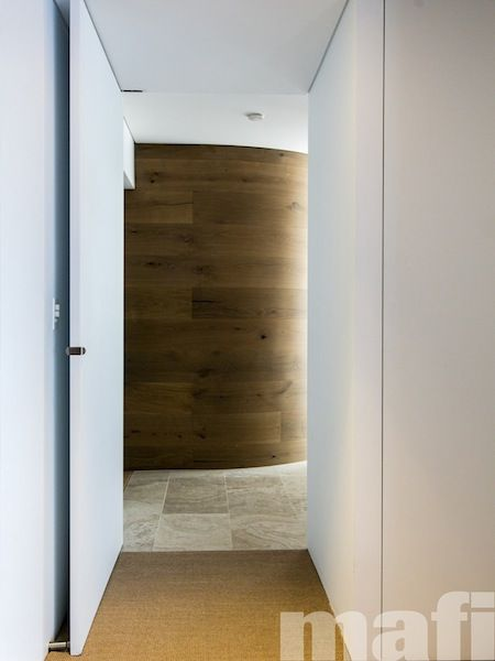 Design firm, C+M Studio explored contrast between different spaces through the use of the mafi curved Oak Country Brushed Grey Oil feature wall, in which doors leading to private spaces were hidden, flush with the finished face of the wall.