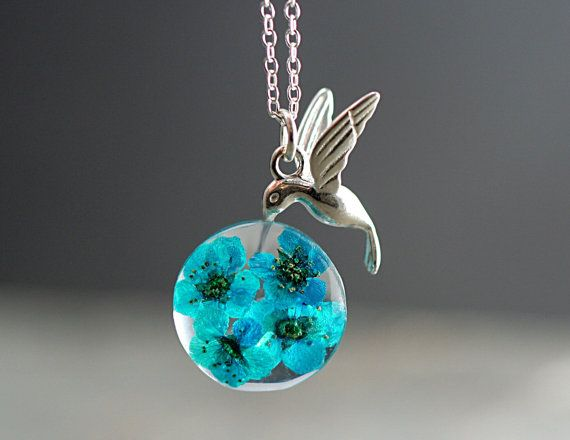 Hummingbirds are able to precisely hover in place. And this is exactly what this unique necklace shows:  Sterling silver necklace with a tiny sterling hummingbird. With his beak, he is feeding from floral nectar. The real turquoise blue blossoms are cast in eco-friendly transparent resin which looks like glass.  Measurements: The chain is 18 The pendant is around 1.  Please note that real flowers cannot be identical. So every necklace will look slightly different. The pictures show two…