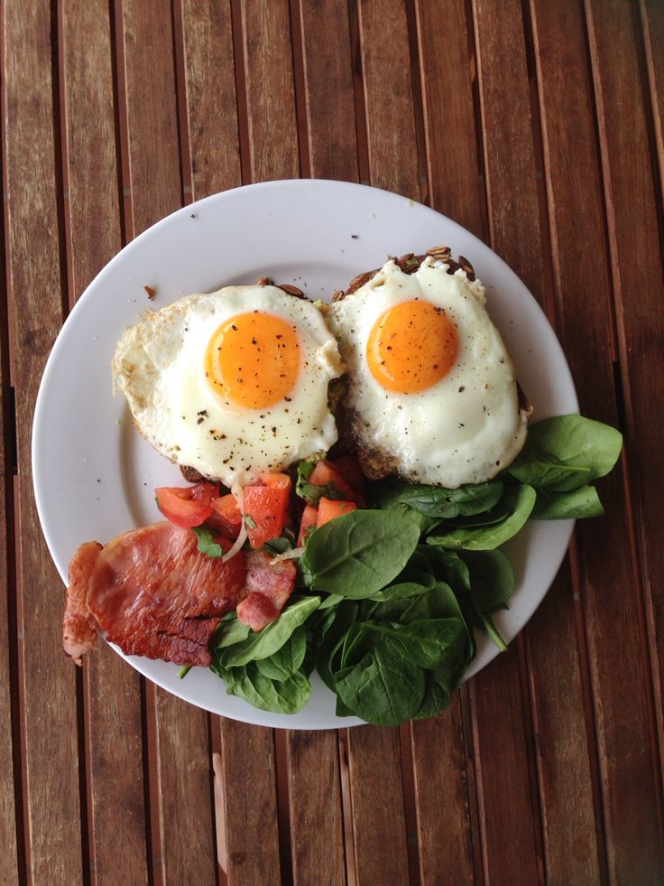 Eggs and avocado on pumpkin seed rye bread, with bacon and spinach leaves