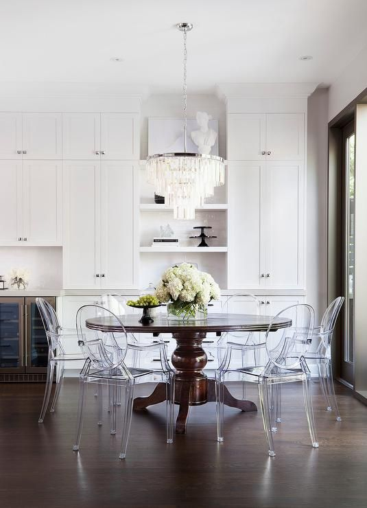 Kartell Host Chairs surround brown round traditional dining table placed beneath a white fringe chandelier.
