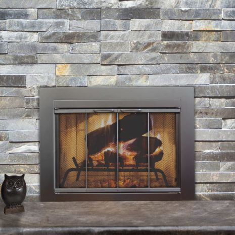 "Fremont Fireplace Door- 3 3/8"" wide by 1"" deep main frame made of 16 gauge steel 3/16"" smoked tempered safety glass with lifetime warranty Overlap fit door Hidden damper for air flow control Mounting hardware included Proudly made in the USA Free shipping - we just keep saving you money! Uniframe construction for strength and lasting quality. No welded joints All Standard fireplace doors need a hearth to sit on! Do not install these fireplace glass doors on any factory-built firebox, prefabs…"