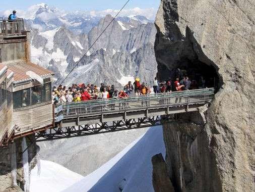 Aiguille du Midi, França. Esta ponte liga o topo de duas belas montanhas dos Alpes franceses. Felizmente, ela é bem curta, porque a altura é para deixar as pernas de qualquer pessoa normal bambas. São 2.800 metros de teleférico para chegar lá.  Fotografia: Reprodução.