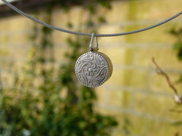 zilveren hanger met als deksel van het doosje een knoop