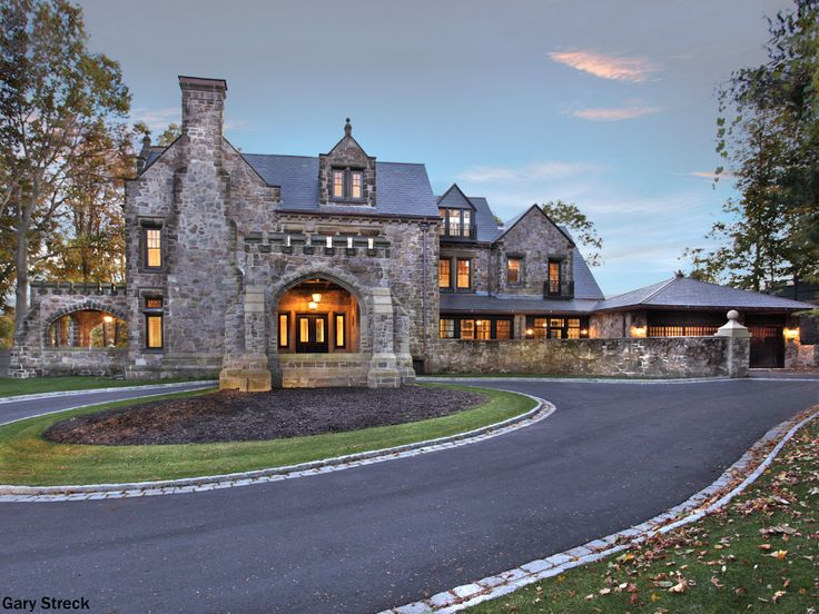 Stone home with a covered drop-off area, a round-about driveway, slate roof and chimney and a renaissance revival touch. The castle look makes it seem like we are in Game of Thrones.