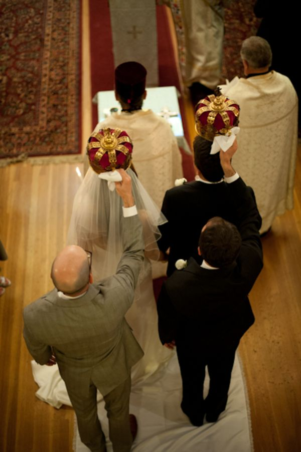 Bride and groom receiving crowns as part of traditional ceremony.