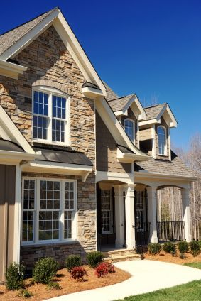 Stone Exterior with cedar shake siding. White Double Hung windows with Colonial Grills