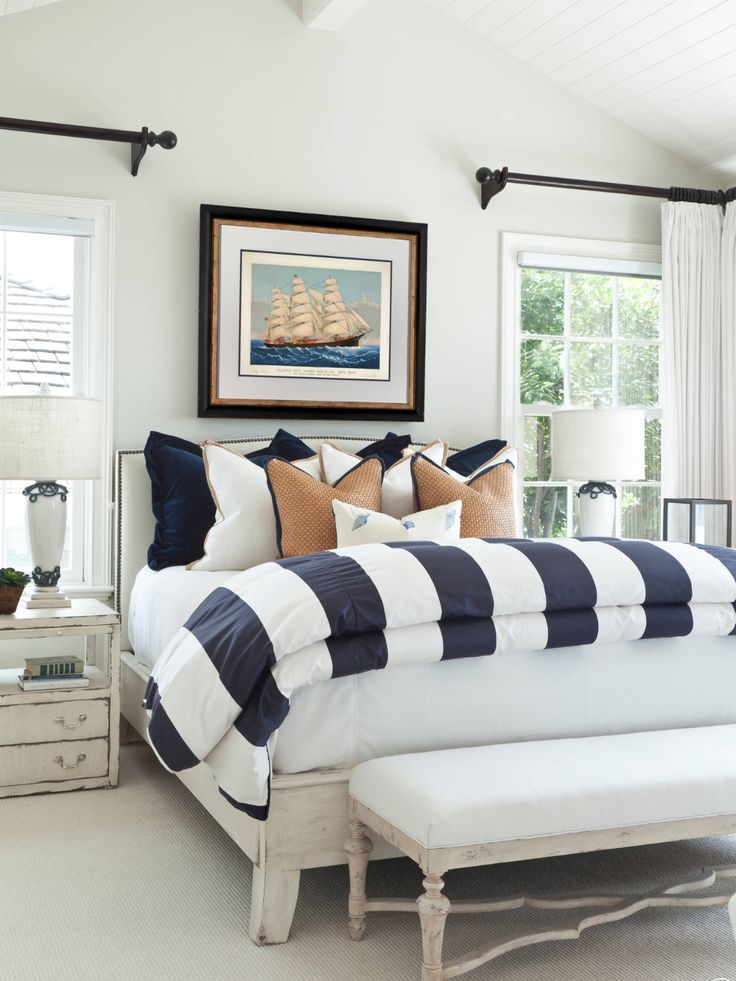Nautical bedroom   white and blue striped bedspread   dark curtain rods with white curtains   framed art over bed