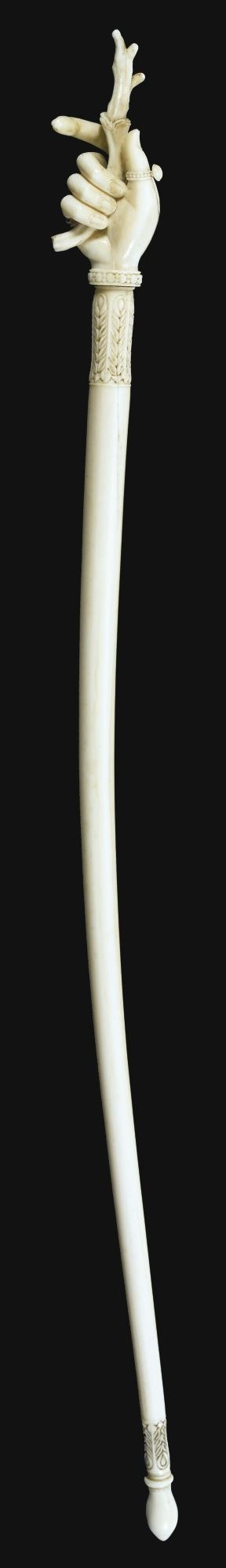 A CARVED IVORY BACK-SCRATCHER, MURSHIDABAD, CIRCA 1800 the ivory carved in the form of a hand wearing a thumb-ring and a pearl bracelet, clasping a gnarled root, antler, or piece of coral, with the extended index finger and part of splayed coral acting as the scratchers, carved palmette motifs to top and bottom of handle   40.2cm.