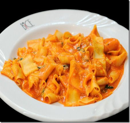 Pappardelle al Telefono, feature large homemade ribbons of pasta lightly dressed with a basil and tomato cream sauce and tossed with hints of mozzarella