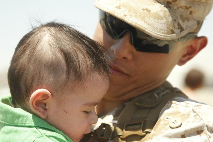 1st Lt. Mark Villanueva, Company B, 1st Tank Battalion holds his 4-month-old son, Mark Jr., for the first time during the unit's homecoming event at the 1st Tanks compound June 2, 2012. The company just returned from their 7-month deployment in Aghanistan. (Official U.S. Marine Corps photo by Cpl. Sarah Dietz/Released)