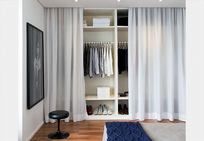 O morador deste apartamento optou por um modelo de armário aberto. Para não deixar a bagunça exposta, resolveu criar uma solução decorativa simples: em vez de portas, encomendou uma cortina de voile branco que corre em trilho embutido atrás da sanca de gesso