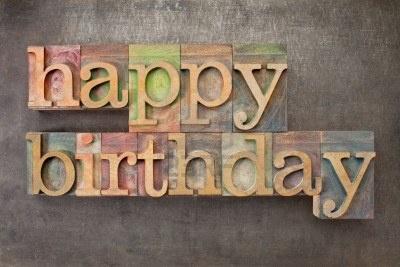 happy birthday - text in vintage letterpress printing blocks against a grunge metal sheet Stock Photo